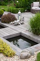 Contemporary Ipe hard wood deck over pond, contrasting texture of rounded pebbles softened by planting of Miscanthus sinensis, Pittosporum ten. 'Tom Thumb'. Euonymus fortunei 'Emerald 'n' Gold' and low Buxus sempervirens hedging