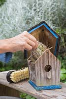 Remove nesting material inside the birdhouse.