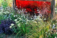 Coloured translucent perspex screens in flower beds. Description: Prehistoric Modernism. Designer: Alex Schofield