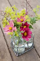 Floral display of cosmos, alchemilla mollis and heuchera flowers in small glass jars