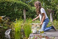 Young girl pond dipping in her garden