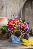 Floral display of rose hips, helianthus seed heads, verbena and chrysanthemum in blue and white tea cup.