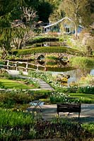 Garden view in springtime with seat bench, litte lake, bridge and garden house