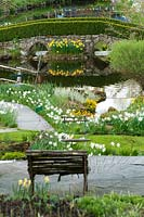 Garden view in springtime with seat bench, lake and bridge