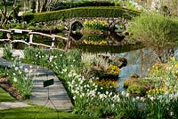 Garden view in springtime with daffodils, little lake, bridge