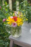 Cut garden flower arrangement - yellow marigolds, crimson flax, pink cornflowers and toadflax in vintage cut glass jug