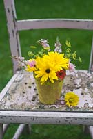 Cut garden flower arrangement - yellow marigolds, crimson flax, fennel and toadflax in yellow flower pot