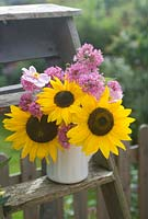Cut garden flower arrangement - sunflowers pink valerian and Japanese anenomes in vintage wooden steps