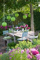 Garden Party in early summer under a walnut tree. Table with Paeonia - peony and lanterns