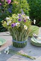 Arrangement of meadow flowers in glass clad with Secale cereale - rye grass. Cut flowers include leucanthemum, alchemilla, centaurea cyanus, dianthus barbatus and nepeta - catmint