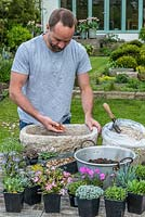 Practical step-by-step guide to planting a stone alpine trough with rock plants. All rock  plants need good drainage, so cover the drainage holes first with crocks - to prevent them becoming blocked and then cover with gravel to a depth of 2-3cm.