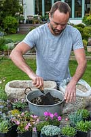 Practical step-by-step guide to planting a stone alpine trough with rock plants. Rock plants need good drainage, so mix half John Innes No. 2 compost with half grit.