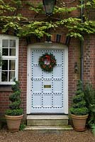 Lovely old front door decorated with a  traditional, long lasting Christmas wreath made using spruce, with red rose hips, dried pumpkins and ribbon.
