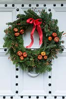 Lovely old front door is decorated with a  traditional, long lasting Christmas wreath made using spruce, with red rose hips, dried pumpkins and ribbon.