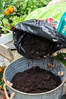 Planting a container herb garden. Step 2: fill the container with potting compost.