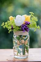A summer posie with everyday flowers - Verbena bonariensis, Alchemilla mollis and yellow and white roses in glass jar decorated with raffia and dried rose buds.