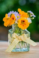 A summer posie of everyday garden flowers - Nasturtium, Aster and Anthemis in a glass jar decorated with yellow gingham ribbon.
