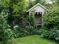 A traditional summer garden with borders filled with roses and perennials with a wooden arbour.