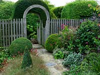 Oak moon gate leads over alley to identical gate beneath yew arch. Box balls and pyramid edged in Gypsophila Rosenschleier, Persicaria bistorta, Persicaria orientalis, Dahlia Moor Place, Fuchsia magellanica, Zinnia Purple Prince, Salvia officinalis Berggarten.
