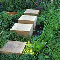 Wood oak cubes form stepping stones through planting and across small wildlife pool.