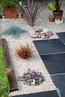 Completed gravel garden with black limestone paving and plants in Summer.