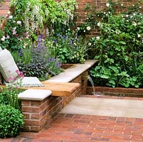 Tiny retreat enclosed by walls. Stone and brick floor. Bench seat with cushions. Stepped water feature. Raised bed: grasses, shrubs and perennials.