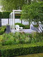 Pergola like wooden frames focus attention on views within the space. Geometric layout of box and hornbeam mixes with perennials and shrubs. Raised patio with chair.