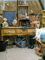 In greenhouse, old pine dresser provides work area for terracotta pots, string, labels, gloves and lists. Boots, watering cans, fork and trug.
