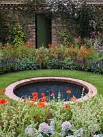 Circular pool in round lawn edged in beds of poppies, eryngium and salvia. Beyond, wall clad in Clematis montana 'Rubens' with door.