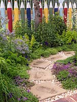 Fun picket fence in shape of coloured pencils edges herb bed of mint, borage, parsley, thyme, chives, oregano, chamomile and strawberry. Paving stones through gravel.