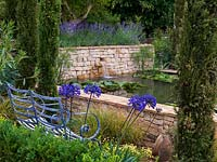 Raised pool, clad in dry stone walls, is home to water lilies. Mediterranean style garden with lavender, agapanthus, cypress, olive, oleander and santolina. Bench.