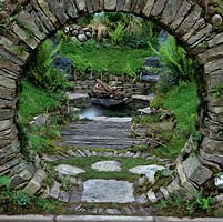 Glimpsed through a circular, dry stone window, a tranquil, personal sanctuary, naturalistic in style, with pool and seats.