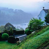 View of the cottage and Japanese-style terrace overlooking the River Dart on a misty morning.