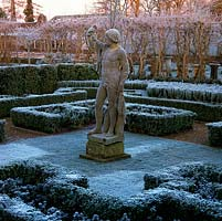 At dawn, C18 stone Apollo by Peter Van Baurscheit overlooks formal parterre of low, clipped box hedges. Behind, line of bare Ginkgo biloba.