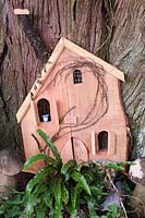 Child's miniature house at the base of a tree with ferns