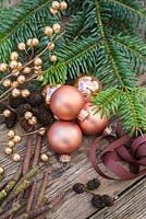 Copper colour themed Christmas decorations. Baubles, ribbon, alder foliage and yew tree foliage