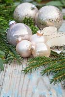 Champagne colour themed Christmas decorations. Baubles, ribbon, yew and cedar foliage