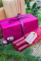 Purple coloured Christmas presents accompanied with Fir and Holly - Ilex foliage