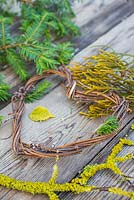 A grapevine heart on a wooden surface, accompanied with Yew foliage, Prunus with Lichen and Conifer foliage