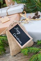 Christmas present wrapped in Hessian, accompanied with Yew foliage. Featuring cork tag and Alder decoration