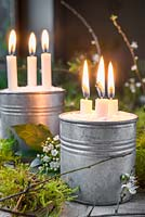 Candles mounted in metal cans containing salt, decorated with moss and Crataegus - Hawthorn blossom.