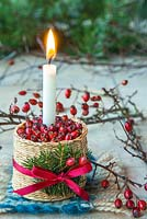 Candle mounted in a woven basket containing Crataegus - Hawthorn berries