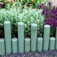 Sawn wooden poles of differing heights create edging to perennials. Poles painted to blend with silvery blue lavender and artemisia.
