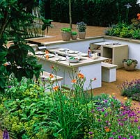 Sunken, outdoor dining area. Stone benches and table. Barbecue. Pots of herbs. Beds of daylily, alchemilla, lavender, agapanthus and herbs. Sunken.