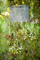 Home-made wind chime with hydrangea flowerheads, allium seedheads, berries and antique silver cutlery