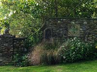 Wall built by John Hawkins from local stone with inset lion mask water spout. In the bed Stipa arundinacea is planted with white flowered Persicaria campanulata Alba Group.