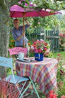 Woman opening parasol - table under an apple tree. Cut flower arrangement in blue enamel bucket -  Zinnia, Anemone hupehensis, Sedum and rose hips