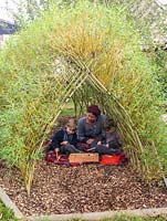 Brothers Jacob and Loui with their mother, Ali Rose, play on the floor in the shade of a tunnel  woven from living Salix viminalis - willow.