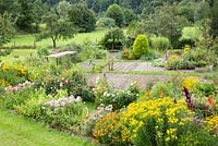 Embedded in a landscape with fruit trees, meadows and a forest, a rural garden plot with perennial borders