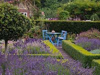 Parterre of four triangular, box-edged beds filled with standard Ilex aquifolium - holly and six different varieties of lavender. At end, tranquil spot with table and chairs.